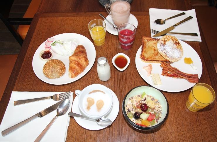 Kaffee, Croissant, Pancakes und Eier zum Frühstück